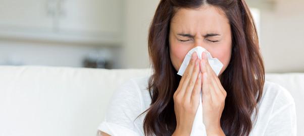Brunette sneezing in a tissue
